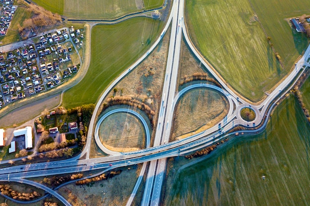 Luftansicht der modernen autobahnstraßenkreuzung, hausdächer auf frühlingsgrünfeld. drohnenfotografie.