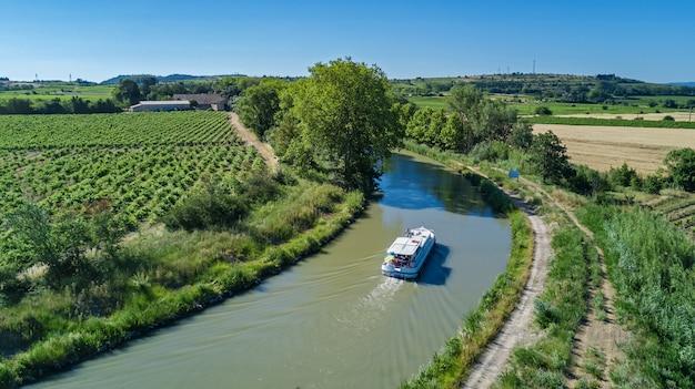 Luftansicht des bootes im canal du midi von oben, familienreise per lastkahn und urlaub in südfrankreich