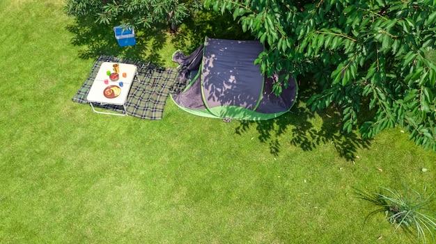 Luftansicht des campingplatzes von oben, zelt- und campingausrüstung unter baum, familienurlaub im camp im freien konzept
