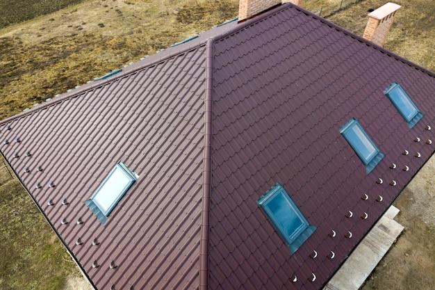 Luftansicht des gebäudes des steilen braunen schindeldachs, der gemauerten schornsteine und der kleinen dachfenster auf hausoberseite mit metallziegeldach. dachdecker-, reparatur- und renovierungsarbeiten.