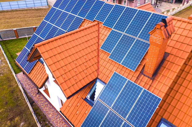 Luftansicht des neuen modernen wohnhaushauses mit blau glänzendem solarfoto-voltaik-paneelsystem auf dach. konzept zur erzeugung erneuerbarer ökologischer grüner energie.