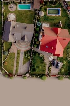 Luftansicht von oben auf ein privathaus mit gepflastertem hof mit grünem grasrasen mit betonfundament.