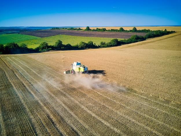 Luftaufnahme auf mähdrescher sammelt den weizen bei sonnenuntergang. getreidefeld ernten, erntesaison. blick auf die erntemaschine auf dem teilweise geernteten feld. sommer, moldawien, europa.
