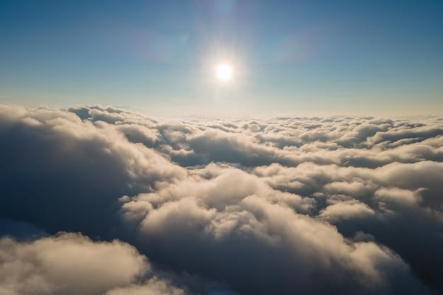Luftaufnahme aus dem flugzeugfenster in großer höhe von dichten geschwollenen kumuluswolken, die sich abends vor dem regensturm bilden.