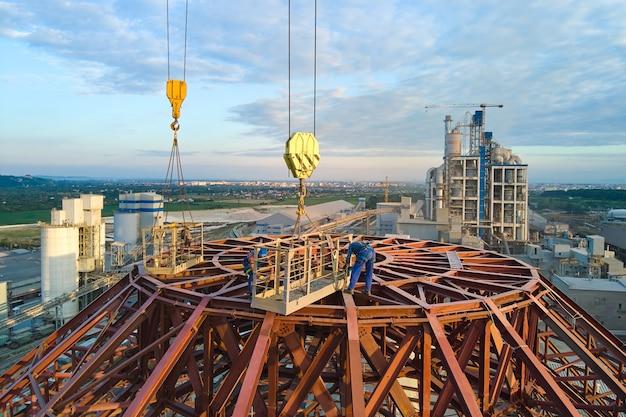 Luftaufnahme der arbeiter in der im bau befindlichen zementfabrik mit hoher betonwerksstruktur und turmdrehkranen im industriellen produktionsbereich.