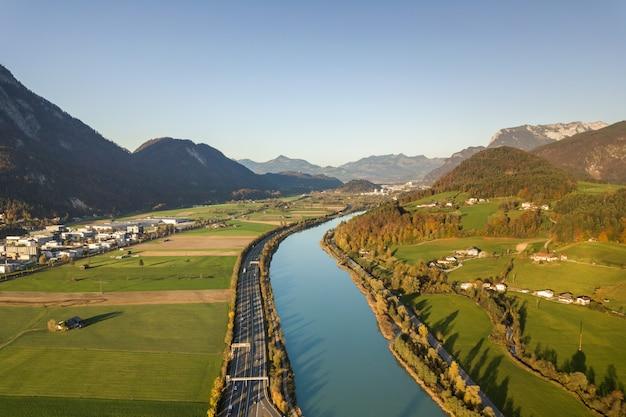 Luftaufnahme der autobahn-autobahn mit schnellem verkehr nahe großem fluss in den alpenbergen