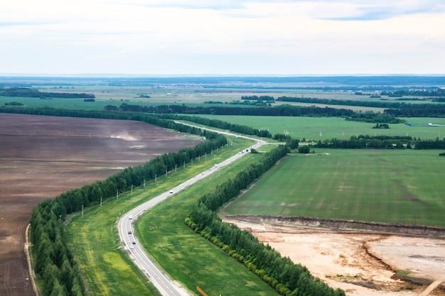 Luftaufnahme der autobahnstraße durch frühlingswaldlandschaft