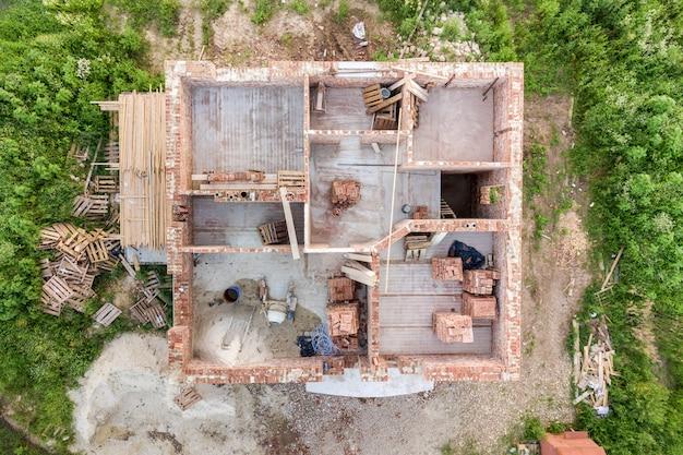 Luftaufnahme der baustelle für zukünftiges haus, ziegelsteinkellerfußboden und stapel ziegelstein für bau.