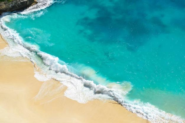 Luftaufnahme der blauen ozeanwelle des meerblicks auf sandigem strand.