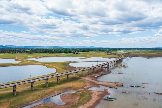 Luftaufnahme der eisenbahnbrücke über einen stausee in pasak chonlasit dam in der sommersaison in lopburi, thailand.