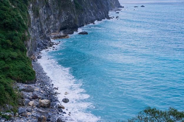 Luftaufnahme der felsigen gebirgsküste mit grünen bäumen und blauem meer mit weißen schäumenden wellen im sommer