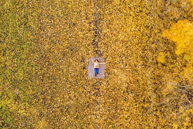 Luftaufnahme der frau, die auf gelben blättern draußen liegt