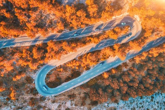 Luftaufnahme der gebirgskurvenstraße mit autos, orangenwald bei sonnenuntergang im herbst