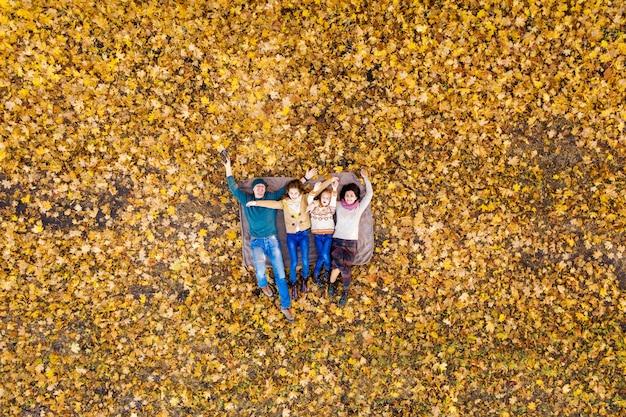 Luftaufnahme der glücklichen familie liegend im herbstpark