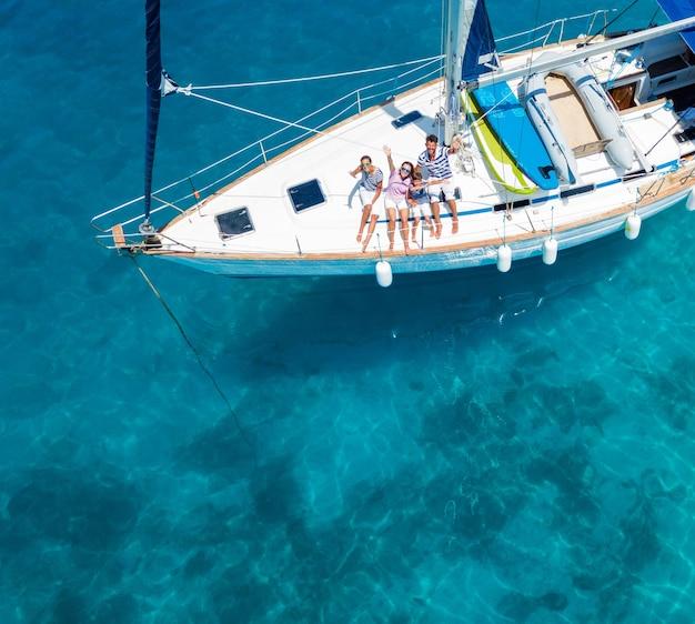 Luftaufnahme der glücklichen familie mit entzückender tochter und sohn, die auf einer großen yacht ruhen