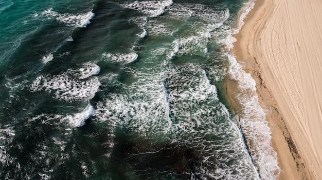 Luftaufnahme der grünen ozeanwellen mit einer sandigen küste