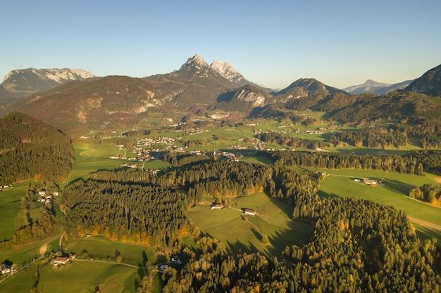 Luftaufnahme der grünen wiesen mit dörfern und wald in den österreichischen alpenbergen.