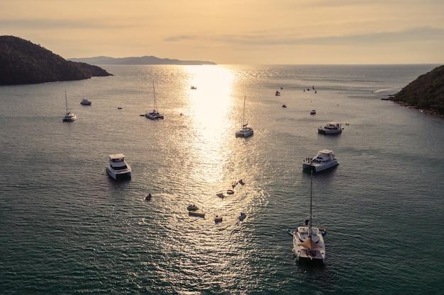 Luftaufnahme der gruppe der privaten yacht, die auf tropischem meer am sonnenuntergang segelt