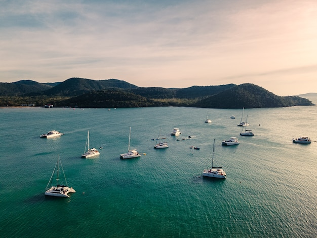 Luftaufnahme der gruppe der privaten yachtkreuzfahrt auf tropischem meer am abend