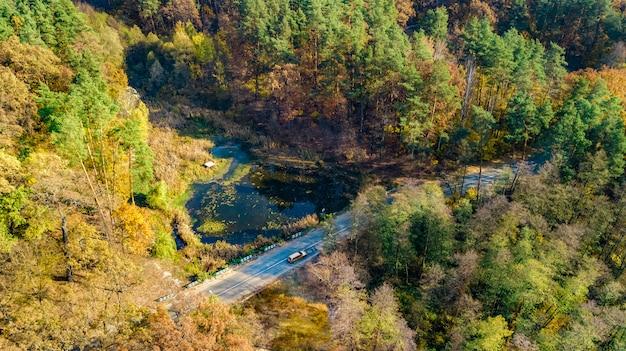 Luftaufnahme der herbstlandschaft und straße von oben, gelbe, grüne und rote goldene herbstbäume und landstraße für autos