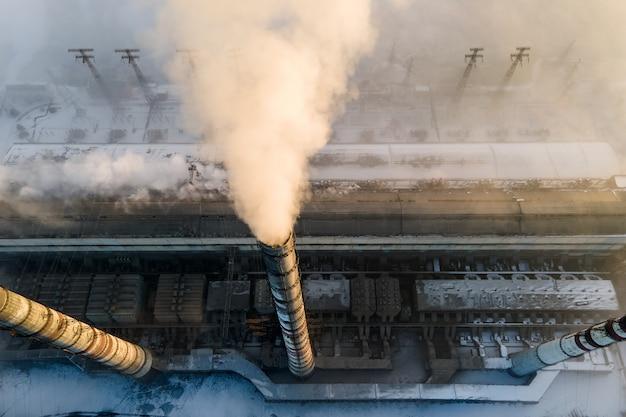 Luftaufnahme der hohen rohre des kohlekraftwerks mit schwarzem rauch, der bei sonnenaufgang die umweltverschmutzende atmosphäre aufsteigt.
