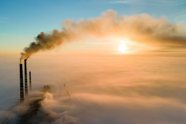 Luftaufnahme der hohen rohre des kohlekraftwerks mit schwarzem rauch, der bei sonnenuntergang die umweltverschmutzende atmosphäre aufsteigt.