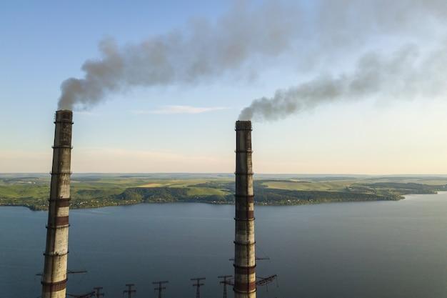 Luftaufnahme der hohen rohre des kohlekraftwerks mit schwarzem rauch, der die umweltverschmutzende atmosphäre nach oben bewegt.