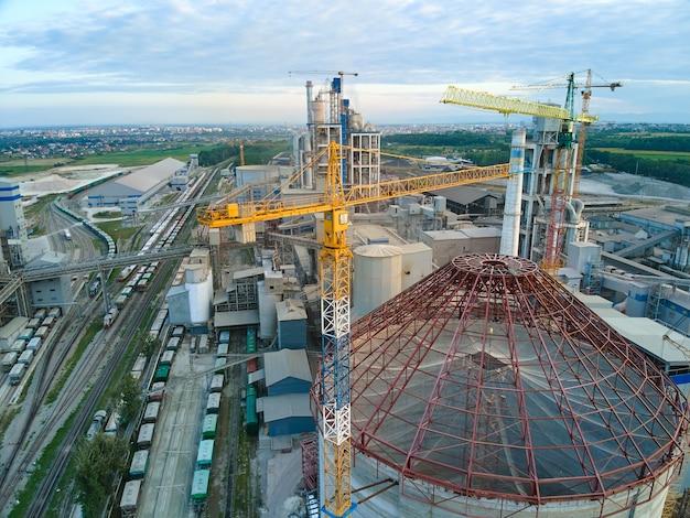Luftaufnahme der im bau befindlichen zementfabrik mit hoher betonwerksstruktur und turmdrehkranen im industriellen produktionsbereich. herstellung und globales industriekonzept.