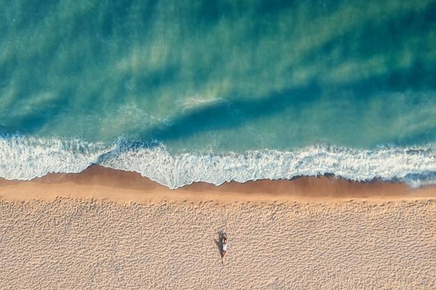 Luftaufnahme der jungen frau mit schönem körper liegt allein am sandstrand mit türkisfarbenem wasser. urlaubsreise und entspannungskonzept draufsicht