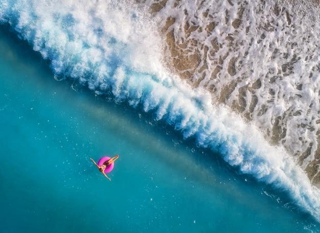 Luftaufnahme der jungen frau schwimmend auf dem rosafarbenen schwimmenring