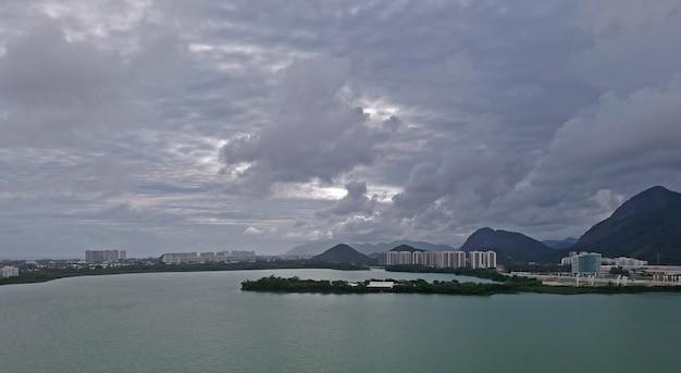 Luftaufnahme der lagune jacarepagua in rio de janeiro. bewölkter tag. berge und gebäude im hintergrund. drohnenfoto.