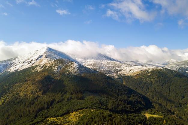 Luftaufnahme der majestätischen berge bedeckt mit grünem fichtenwald und hohen schneebedeckten gipfeln.