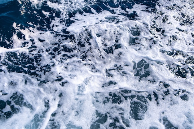 Luftaufnahme der meerwasseroberfläche von oben nach unten. weißer schaumwellen textur als natürliche wand.