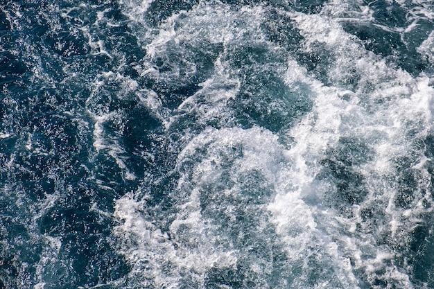 Luftaufnahme der meerwasseroberfläche von oben nach unten. weißer schaumwellenbeschaffenheit als natürlicher hintergrund.