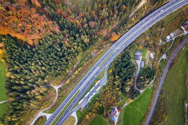 Luftaufnahme der oberen morgendämmerung der autobahngeschwindigkeitsstraße zwischen gelben herbstwaldbäumen im ländlichen bereich.