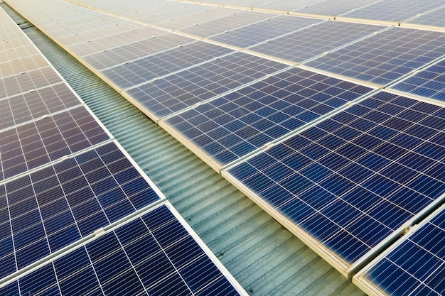 Luftaufnahme der oberfläche von blauen photovoltaik-solarmodulen, die auf dem gebäudedach montiert sind, um sauberen ökologischen strom zu erzeugen. konzept zur erzeugung erneuerbarer energien.