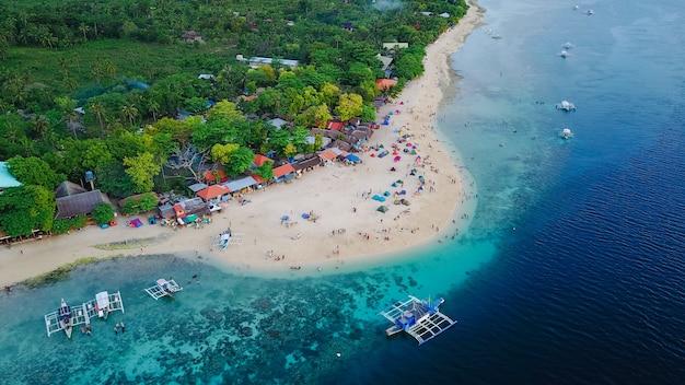 Luftaufnahme der sandstrand mit touristen schwimmen in wunderschönen klaren meerwasser der sumilon insel strand landung in der nähe von oslob, cebu, philippinen. - farbverarbeitung steigern
