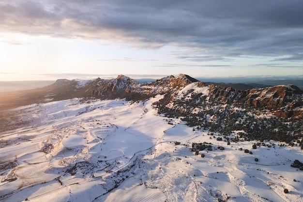 Luftaufnahme der schneebedeckten berge bei sonnenuntergang