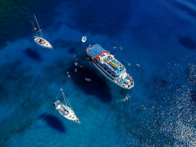 Luftaufnahme der schönen blauen lagune am heißen sommertag mit segelboot. draufsicht der leute schwimmen um das boot.