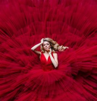 Luftaufnahme der schönen blondine liegt in einem roten kleid, das das ganze foto ausfüllt
