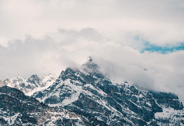 Luftaufnahme der schönen felsigen schneebedeckten berge, die in den wolken bedeckt sind