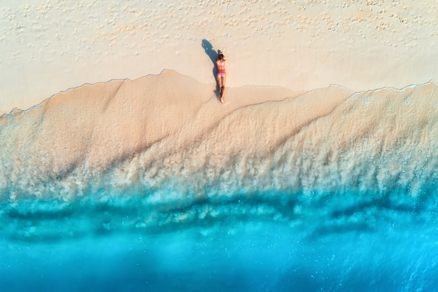 Luftaufnahme der schönen jungen liegenden frau auf dem weißen sandstrand nahe meer mit wellen bei sonnenuntergang. sommerferien. draufsicht auf den rücken des sportlichen schlanken mädchens, klares azurblaues wasser. sexy gesäß. entspannen