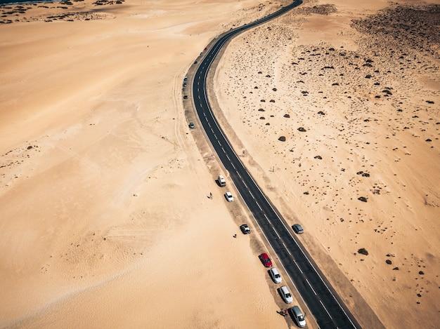Luftaufnahme der schwarzen asphaltstraße mitten am strand - wüste herum und konzept von reisen und urlaub. tropischer malerischer ort - transport und geparkte autos in wilder landschaft