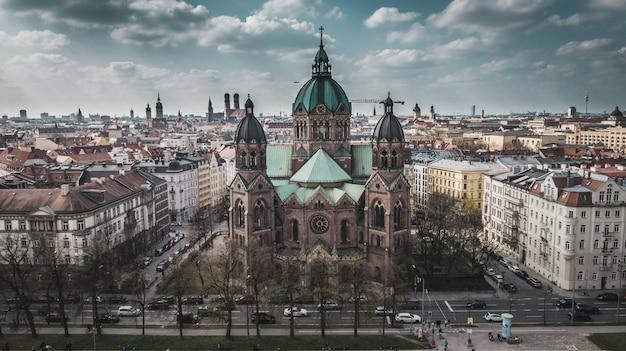 Luftaufnahme der st. lukas kirche und im hintergrund münchener stadt in bayern, deutschland.
