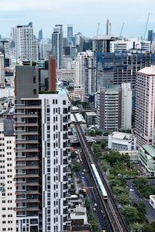 Luftaufnahme der stadt bangkok mit überfülltem gebäude und öffentlichem skytrain bei thailand