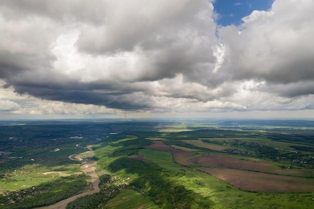 Luftaufnahme der stadt oder des dorfes mit reihen der gebäude und der curvy straßen zwischen grünen feldern am sommer. landschaftslandschaft von oben.