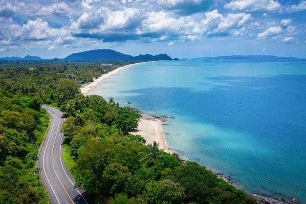 Luftaufnahme der straße zwischen kokospalme und großem ozean zur tageszeit in nakhon si thammarat, thailand