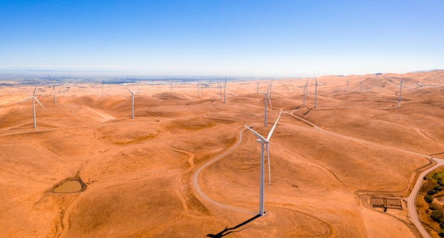Luftaufnahme der windturbinen und der kurvigen straße auf schöner goldener berglandschaft in kalifornien