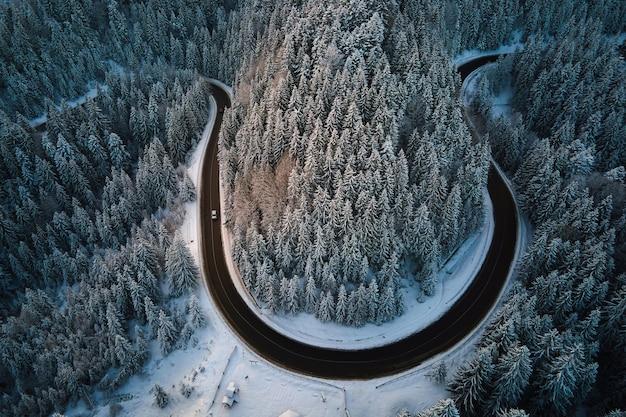 Luftaufnahme der winterlandschaft mit schneebedeckten berghügeln und kurvenreicher forststraße am morgen.