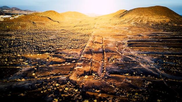 Luftaufnahme der wüstenlandschaft mit bergen und sonnenuntergang